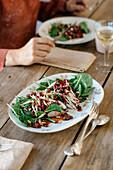 Spinatsalat mit karamellisierten Schalotten, Portwein-Rosinen und gerösteten Pinienkernen