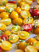 Yellow and red tomatoes with thyme on a baking tray