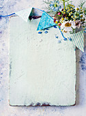 White-painted wooden board decorated with bunting and wildflowers