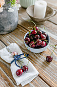 A candle, a vase, a bowl of cherries and fabric napkins on a wooden table