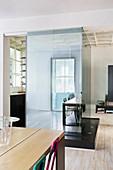 Blick vom Wohnbereich auf Miniküche abgetrennt durch Glaswände