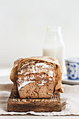 Rye bread on a wooden board with a milk bottle in the background