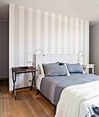 Doppelbett vor grau-weiß gestreifter Trennwand