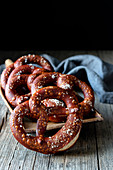 Fresh appetizing pretzels with salt arranged on scoop over old wooden surface