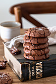 Stack of homemade chocolate brownie cookies and cookbook on wooden table against blurred background