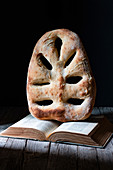 Loaf of fresh fougasse bread placed on open recipe book on wooden table against black background