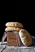Fresh pita flatbread placed on napkin and wooden blocks on rustic table against black background