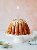 Lemon Drizzle Cake als Geburtstagskuchen mit Kerze und Zuckerglasur