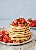 Ein Stapel Pancakes mit Erdbeeren, Pfirsichen, Granola und Ahornsirup