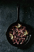 Grilled squids calamari tentacles with lemon in cast iron pan over black concrete background