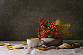 Cup of espresso coffee, autumn leaves, berries in ceramic vase, coffee beans and shortbread cookies