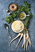 Parsnip cream soup in ceramic bowl with butter sauce, bagel bread, bundle of fresh parsnip and herbs