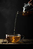 Tea being poured from a glass teapot into a cup