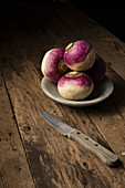 Raw turnips in a bowl on a rustic wooden surface