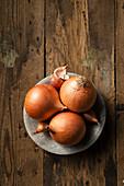 Speisezwiebeln auf Teller und Holzuntergrund