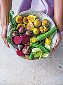 Hands holding a bowl of mini zucchini, figs, patissons and beetroot