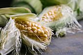Top view of steps of fresh ripe corn peeling on black table