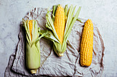 Top view of steps of fresh ripe corn peeling on grey table cloth