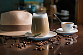 Delicious aromatic brown beverage with white foam in glass on round saucer standing among roasted coffee beans beside hat with brim on wooden glossy table