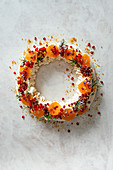 Meringue wreath with whipped cream, pomegranate, satsumas, redcurrants and praline