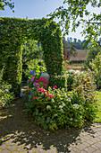 Formschnitt als Torbogen, Beet mit Rosen und Hortensien