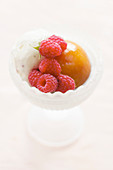 Frosted glass dessert bowl with a scoop of vanilla ice cream, a poached whole peach and freshly picked raspberries