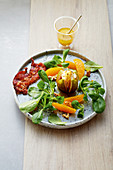 Gratinated figs with goat's cheese, bacon, orange fillets and lamb's lettuce
