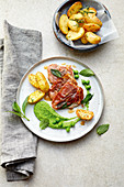 Saltimbocca alla romana with rosemary potatoes and mushy mint peas