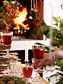 A couple toasting with red wine at a Christmas buffet in front of a fireplace