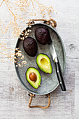 Whole and halved avocados on a vintage zinc tray
