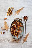 Getrocknete Apfelspalten auf Zinktablett mit Weihnachtsdeko