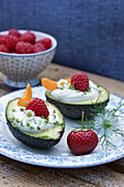 An avocado filled with herb cream and fruit