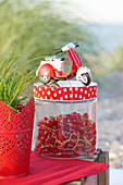 A Vespa model on top of a screw-top jar of redcurrants on a table on the beach