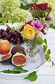 Fruit next to a bouquet of summer flowers in a vase on a table