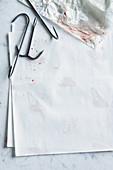 Meat hooks on white paper