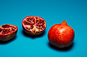 Whole and halved pomegranates in front of a blue background
