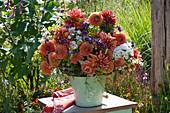 Strauß aus Dahlien, Flammenblume, Fenchel, Eisenkraut und Feinstrahl auf Hocker im Garten