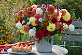 Strauß aus Dahlien, Zinnien, Sonnenbraut, Knöterich und Aster, Teller mit aufgeschnittener Melone