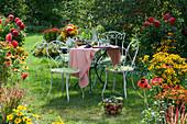Sitzgruppe im Garten zwischen Beeten mit Dahlien, Scheinsonnenhut, Sonnenbraut und Sonnenhut, Korb mit Äpfeln und Weintrauben