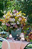 Herbstlicher Strauß aus Herbstanemone, Fetthenne, Goldrute, Sonnenbraut, Sonnenhut, Himbeeren und Blüten vom Chinaschilf
