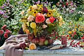 Spätsommer-Strauß aus Rosen, Sonnenhut, Fenchel, Goldrute, Hagebutten und Himbeeren in Drahtkorb mit Äpfeln
