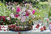Spätsommer-Strauß aus Rosen, Herbstanemonen. Fetthenne und Aster, Äpfel, Hagebutten und Brombeeren auf dem Tisch