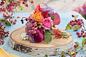 Kleiner Herbststrauß auf Holzscheibe: Rosen, Astern, wilder Wein, Fetthenne, Pfaffenhütchen und Knallerbsen