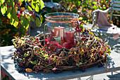 Kranz aus Ranken vom wilden Wein und Zweigen von vielblütiger Rose mit Windlicht