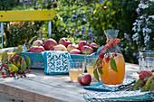 Tablett mit frisch gepflückten Äpfeln, Dekanter und Gläser mit Apfelsaft, Zieräpfel als Deko