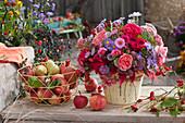 Herbststrauß aus Rosen, Astern, Fetthenne, Hagebutten und Pfaffenhütchen, Korb mit Äpfeln und Birnen