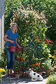 Frau gießt Kasten mit Quamoclit, Scheinsonnenhut, Grünkohl, Chili und Kapuzinerkresse, Töpfe mit Chilipflanzen und Salbei, Hund Zula