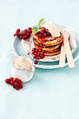 Small pancakes with cream, icing suger and red currants