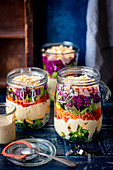 Layered salad in a jar - broccoli, eggs, sauce, peper, carrot, lettuce, purple cabbage, ham, cheese