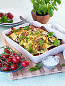 Pasta gratin with mushrooms, tomatoes and peas